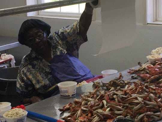 Thelma Coston sings while she works at Nandua Seafood LLC in Hacks Neck, Virginia on Wednesday, July 4, 2018.