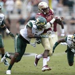 FSU's Dalvin Cook breaks through USF defenders Johnny Ward, right, and Tajee Fullwood for a 74-yard touchdown run during their game at Doak Campbell Stadium on Saturday, Sept. 12, 2015.