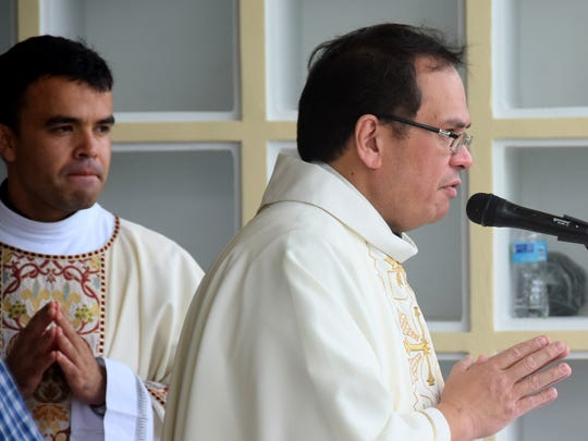 In this 2014 photo, Father Adrian Cristobal gives an opening prayer at All Souls' Day Mass at Guam Memorial Park in Barrigada. He was reassigned to the Umatac church.