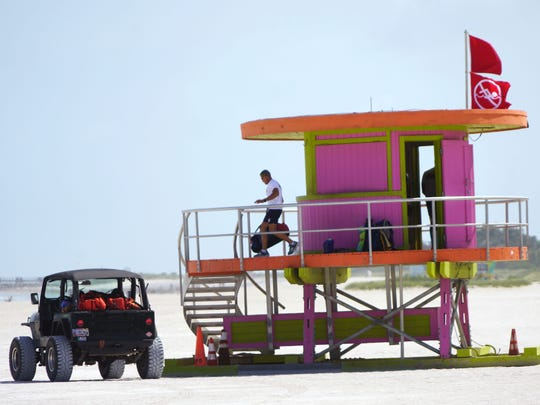 A lifeguard removes gear from a guard hut on South Beach in Miami on Sept. 8, 2017, as two red flags fly, warning of dangerous surf and a ban on swimming.