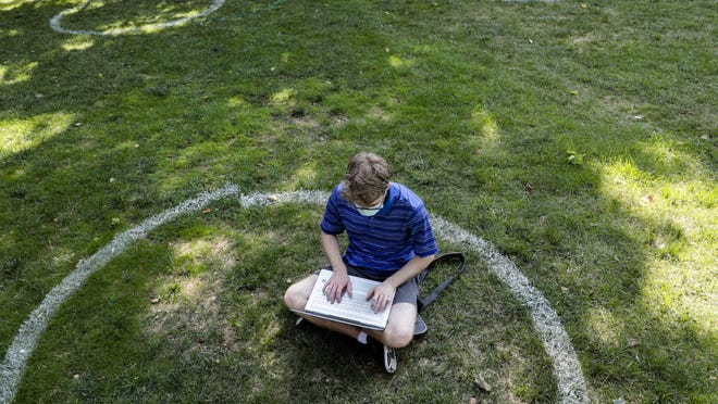 """Logan Armstrong, a Cincinnati junior, works while sitting inside a painted circle on the lawn of the Oval during the first day of fall classes on Tuesday, Aug. 25, 2020 at Ohio State University in Columbus, Ohio. Classes this semester are a mix of virtual and in-person because of the ongoing COVID-19 pandemic. Students wore masks across campus and were reminded to socially distance to prevent the spread of the novel coronavirus. The circles were painted throughout the Oval to allow students to maintain social distance while sitting on the lawn. """"I'm actually glad the school put these,"""" Armstrong says of the circles. """"It shows they're taking this seriously."""""""
