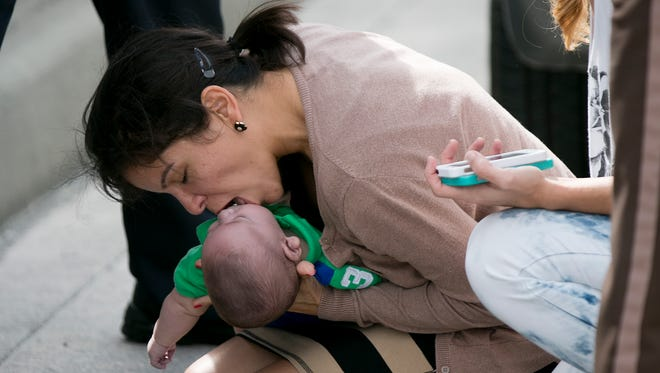 Pamela Rauseo, 37, performs CPR on her nephew, five-month-old Sebastian de la Cruz, after pulling her SUV over on the side of the road along the west bound lane on Florida State Road 836 on Feb. 20, 2014.