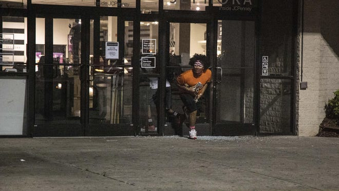 A looter flees from the JC Penney store at Cross Creek Mall in Fayetteville on May 30.