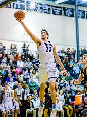 Brandon Johns ,23, of East Lansing lays the ball up to give East Lansing a 63-62 lead over Jaron Faulds ,right, and his Holt teammates with lees then 2 minutes remaining in their game Friday in East Lansing.