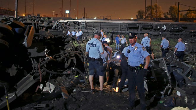 Emergency personnel investigate the wreckage of an Amtrak train  that derailed and crashed in Philadelphia, Tuesday.