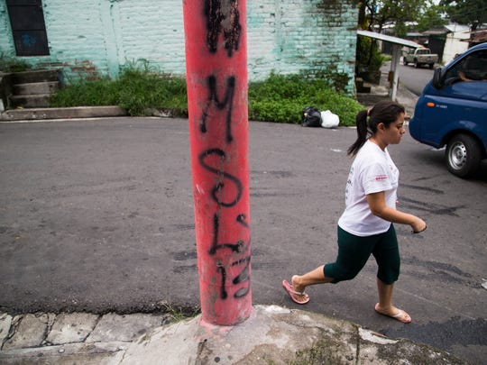 A woman walks past gang grafitti in a neighborhood controlled by the MS-13 gang in San Salvador, El Salvador June 19. Violent crime has sent increasing numbers of people from Central America to the U.S., including unaccompanied minors and families.Lack of jobs also drives some migrants.