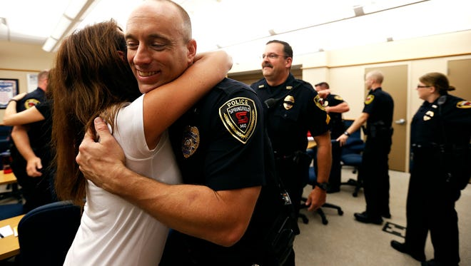 "Janet Reid, a member of local club ""More Wishes and Hugs,"" hugs police officers after the club donated dinner for the Springfield Police Department on July 12, 2016."