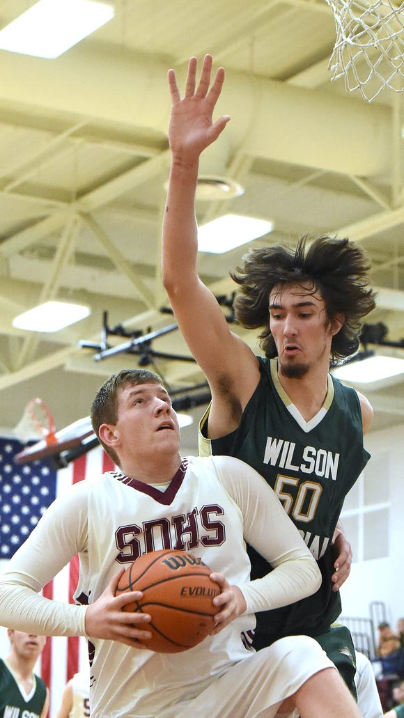 Stuarts Draft's Zach Cook comes away with the rebound and will shoot again as Wilson Memorial's Dean Shaner guards during a basketball game played in Stuarts Draft on Friday, Jan. 2, 2015.
