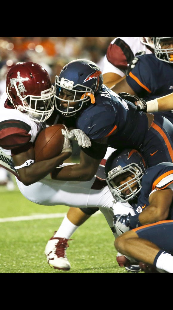 UTEP's Alvin Jones, top, and a teammate tackle NMSU