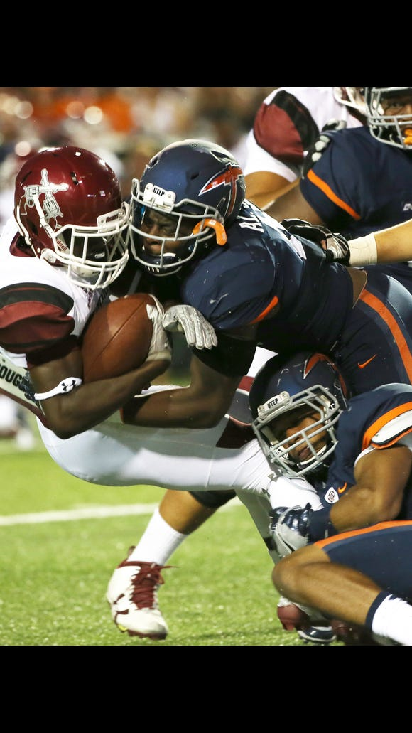 UTEP's Alvin Jones, top, and a teammate tackle NMSU ballcarreier Jason Huntley during the second quarter of last year's game.