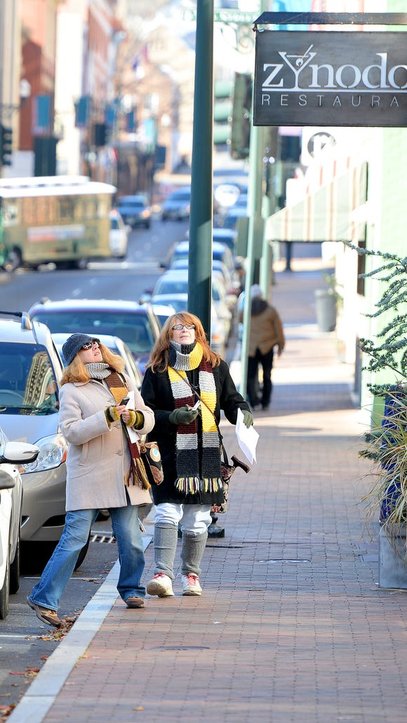 Elizabeth Massie and Hilary Jeffers of Waynesboro both spot the martini glass in the design of the sign for Zynodoa Restaurant. They participate in a visual scavenger hunt hosted by News Leader chief photographer Mike Tripp in downtown Staunton on Saturday, Nov. 15, 2014. Armed with a list of items to find, participants had to locate the items on specific streets and then photograph the object as evidence of finding it.