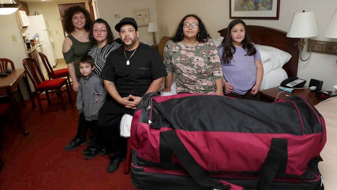 In a Friday, Dec. 1, 2017 photo, from left, Tatiana Morales, her mother, Amanda Naylor, brother Jose, father Jose and sisters Tyeisha and Ellena occupy a single motel room at the Homestead Lodge on the Black Horse Pike in Pleasantville, NJ, after a fire damaged their home and forced them out. To rent a three-bedroom apartment would cost them about $1,500 a month.  (Vernon Ogrodnek/The Press of Atlantic City via AP)