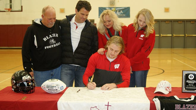 N.E.W. Lutheran senior Gabe Lloyd signs to accept a preferred walk-on offer from the University of Wisconsin football team on Wednesday. Also pictured from left to right are N.E.W. Lutheran football coach Dick Hasseler; Lloyd's father, Doug; Lloyd's mother, Angela Kornowski, and Lloyd's sister, Lydia.