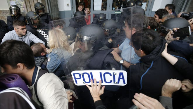 Spanish police officers clash with people outside a polling station in Barcelona, on Oct. 1, 2017.