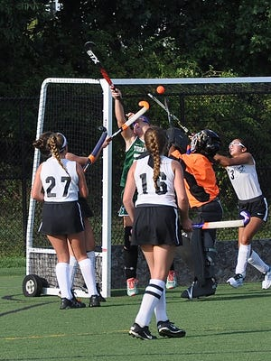 Pawling's Frankie Fleming (l) redirects deflected ball into the net past Yorktown goalie Olivia Sanchez as Fleming's teammate, Isabela Sanchez (13) also tries to get her stick on the ball.