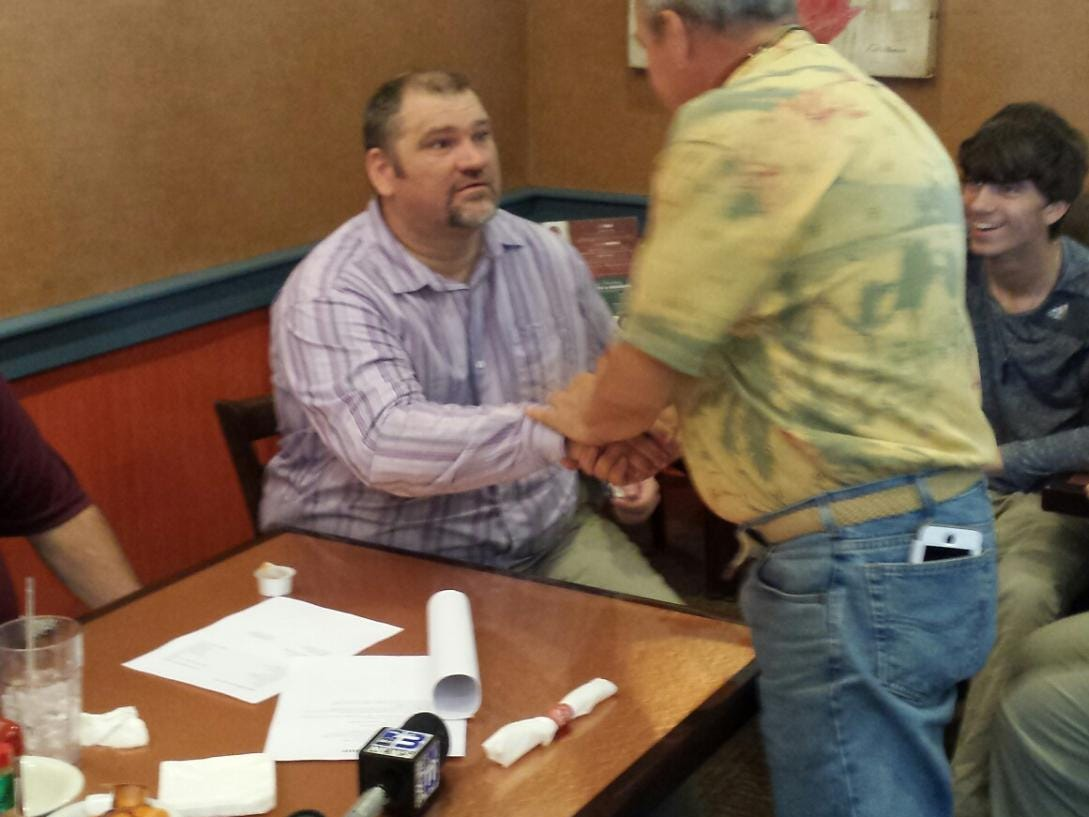 Jamie Rigdon shakes hands with a PHS booster at a press conference at Another Broken Egg Cafe on Tuesday.