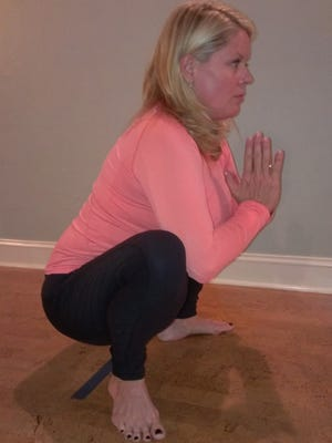 Suzy Goldberg of Ruby and Pearls Yoga Studio, Fort Myers, demonstrates the three stages of Crow Pose.