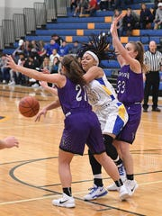 Lexington's Emilee Parker and Olivia Kearns pressure Ontario's Nashail Shelby as she looks to pass the ball in Wednesday's game. Shelby scored a game-high 22 points, but Lex won the game 48-40.