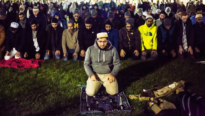 Sadeeque Mohamed of the Muslim Students' Association at the University of Michigan leads a group Isha (evening) prayer on the Diag Monday. Hundreds of U-M students gathered to protect the praying group.