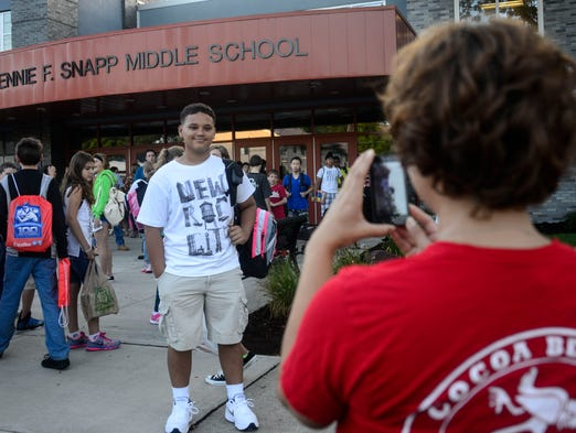 Gregloria Vazquez, of Endicott, takes a photo of her 13-year-old son Kobe Moody before the start of his first day as an eighth grader at Jenne F. Snapp Middle School.
