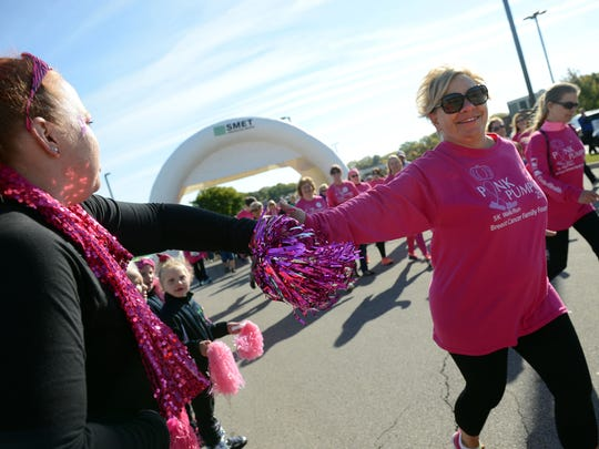 Sue Paulick, right, of De Pere gives a high-five to a cheering supporter during the annual Pink Pumpkin 5K Walk/Run to support the Breast Cancer Family Foundation on Oct. 10 at Northeast Wisconsin Technical College in Green Bay.