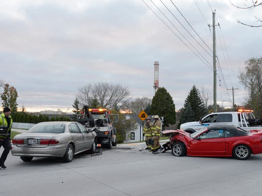 Two cars involved in an accident at the intersection of Spring and Huron streets are towed away from the scene on Friday, Nov. 13.