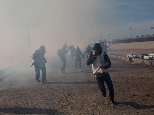 Los migrantes huyen del gas lacrimógeno que lanzaron los agentes de EE. UU. entre fotógrafos y periodistas que cubrían la frontera entre los dos países, después de que un grupo de migrantes logró rebasar a la policía mexicana en el cruce de El Chaparral, en Tijuana, México, el domingo 25 de noviembre de 2018. El alcalde de Tijuana declaró una crisis humanitaria en su ciudad fronteriza, y dijo haberle pedido ayuda a la Organización de Naciones Unidas para ayudar a aproximadamente 5,000 migrantes centroamericanos que llegaron a su ciudad.