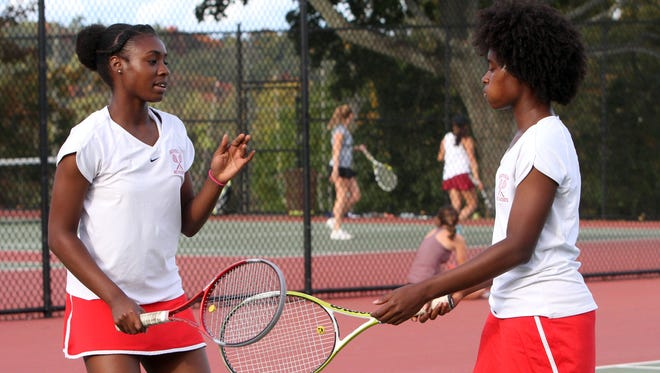 Anika Dwyer and Akemi Dwyer from North Rockland High School tap racquets as they battle Brittany Sedlak and Marisa Magliato from Ursuline, at the Conference II tennis tournament at White Plains High School, Oct. 14, 2015.