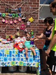 "Education reporter Leigh Guidry and husband Eric get a photo of their daughter, Avery, in her shades and bathing suit at her ""under the sea"" birthday party Saturday. Guidry put together the net behind the present table several times, much to her chagrin."