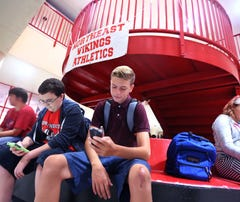 Northeast High freshmen Colton Grainger, 14, left, and Matthew Miller, 14, use their phones before class. Pinellas students will now rely on data for the Web.