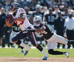 OAKLAND, CA - SEPTEMBER 14:  Running back Arian Foster #23 of the Houston Texans catches a pass for nine yards against safety Charles Woodson #24 of the Oakland Raiders in the first quarter on September 14, 2014 at O.co Coliseum in Oakland, California.  The Texans won 30-14.