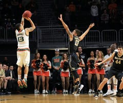 Miami Hurricanes guard Angel Rodriguez (13) makes a three point basket over Wake Forest Demon Deacons guard Mitchell Wilbekin (10) during the first half at BankUnited Center.