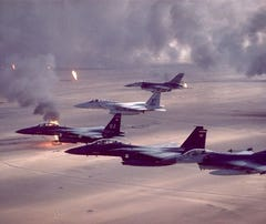 F-16A Fighting Falcon, F-15C Eagle F-15E Strike Eagle fighters fly over burning oil fields in Kuwait during Operation Desert Storm.