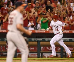 Sep 12, 2015; Anaheim, CA, USA; Los Angeles Angels first baseman C.J. Cron (24) runs the bases after hitting the go-ahead home run off of Houston Astros pitcher Will Harris (left) during the eighth inning at Angel Stadium of Anaheim. Mandatory Credit: Kelvin Kuo-USA TODAY Sports