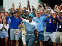 Tiger Woods reacts after chipping in for biride on the 10th hole during the first round of the Wyndham Championship at Sedgefield Country Club in Greensboro, North Carolina.