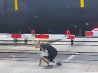 Video captures man rolling under moving train
