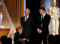 In this Nov. 8, 2014, photo, actress Maureen O'Hara accepts her honorary Oscar onstage as presenters Clint Eastwood, center, and Liam Neeson look on during the 2014 Governors Awards in Los Angeles.