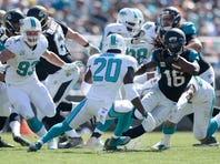 Oct 26, 2014; Jacksonville, FL, USA; Jacksonville Jaguars running back Denard Robinson (16) carries the ball against the Miami Dolphins in the first quarter at EverBank Field. Mandatory Credit: Richard Dole-USA TODAY Sports