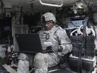 A Cyber Soldier assigned to the 780th Military Intelligence Brigade prepares his equipment inside a Stryker vehicle during an integrated cyber exercise at Joint Base Lewis-McChord, Washington Oct. 21, 2015. The training integrates infantry ground units with cyber, signal and human intelligence collection capabilities, which gives units on the modern battlefield a broader capacity to search out and isolate their enemies in real time.
