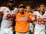 Clemson Tigers head coach Dabo Swinney sings the alma-mater with players Kevin Dodd (98) and Seth Ryan (85) after a game against the North Carolina State Wolfpack at Carter Finley Stadium. Clemson won 56-41.