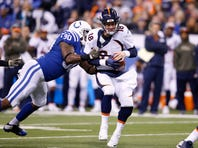INDIANAPOLIS, IN - NOVEMBER 8: Peyton Manning #18 of the Denver Broncos is sacked by Kendall Langford #90 of the Indianapolis Colts in the second half of the game at Lucas Oil Stadium on November 8, 2015 in Indianapolis, Indiana. The Colts defeated the Broncos 27-24.