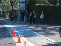 """People await for law enforcement to give the """"all clear"""" signal at Naval Medical Center San Diego."""