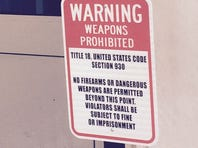 A sign posted at the northwest gate of the White House warns visitors about the firearms law.