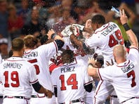 Atlanta Braves third baseman Adonis Garcia (center) is mobbed by teammates after hitting a game winning two run home run against the San Francisco Giants during the twelfth inning at Turner Field. The Braves defeated the Giants 9-8 in 12 innings.