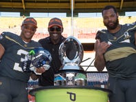 January 31, 2016; Honolulu, HI, USA; Team Irvin quarterback Russell Wilson of the Seattle Seahawks (3), alumni captain Michael Irvin (center), and defensive end Michael Bennett of the Seattle Seahawks (72) pose with the championship trophy after the 2016 Pro Bowl game at Aloha Stadium. Team Irvin defeated Team Rice 49-27. Mandatory Credit: Kyle Terada-USA TODAY Sports