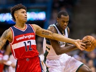 Feb 11, 2016; Milwaukee, WI, USA; Washington Wizards forward Kelly Oubre Jr. (12) and Milwaukee Bucks guard Khris Middleton (22) chase a loose ball during the first quarter at BMO Harris Bradley Center. Mandatory Credit: Jeff Hanisch-USA TODAY Sports