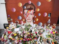 Floral tributes are seen beneath a mural of British singer David Bowie, painted by Australian street artist James Cochran, aka Jimmy C, the day after the announcement of Bowie's death, in Brixton, south London.