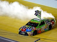 Nov 22, 2015; Homestead, FL, USA; Sprint Cup Series driver Kyle Busch (18) celebrates after winning the NASCAR Sprint Cup Championship after the Ford EcoBoost 400 at Homestead-Miami Speedway. Mandatory Credit: Peter Casey-USA TODAY Sports