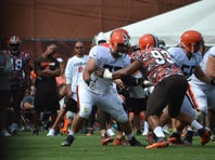 Browns right guard John Greco blocks defensive tackle John Hughes in Thursday's training-camp practice.