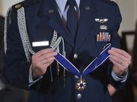 FILE: A military aide holds the Medal of Freedom during a presentation ceremony.
